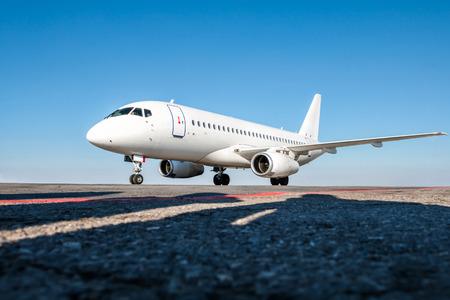 White passenger jet plane on the airport apron