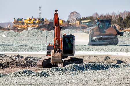 Orange excavator and yellow bulldozer dredges rubble at road construction