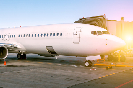 White passenger aircraft parked to a jetway Stock Photo