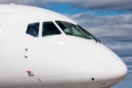 Close view of the cockpit of a white passenger plane outside