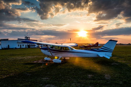 Small private airplanes on the airfield against the backdrop of a colorful sunset Фото со стока
