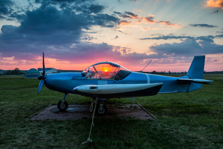 A small sports airplane parked at the airfield at scenic sunset Фото со стока