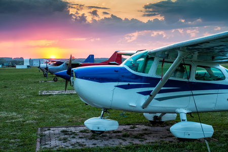 Small private aircrafts parked at the airfield at picturesque sunset