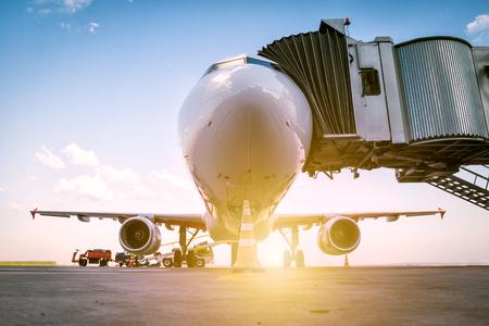 Un avion de ligne blanc se tient à la passerelle d'embarquement et est chargé de bagages sous les rayons du soleil du matin