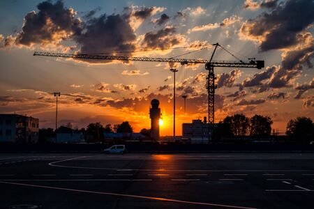 Tower crane on the background of a picturesque sunrise in an empty airport