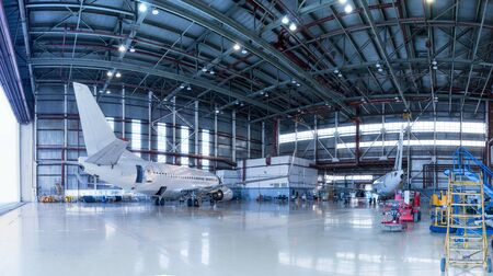 Passenger aircrafts under maintenance. Checking mechanical systems for flight operations. Panorama of airplanes in the hangar Stok Fotoğraf