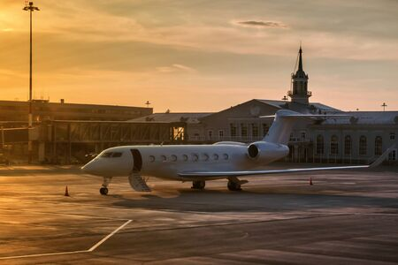 Business plane with the door open by a ladder in the golden evening light on the airport apron near the terminal Фото со стока
