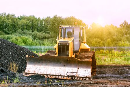 Bulldozer dredges rubble on road construction in the lights of morning sun 写真素材