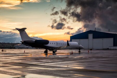 Business jet at sunset after the rain on the airport apron near the hangar Stock fotó