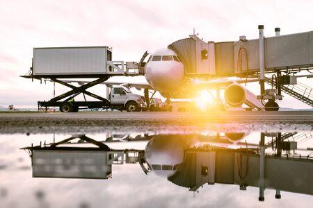 La manutention au sol d'un avion de ligne blanc près de la passerelle d'embarquement au soleil du matin. Chargement de la restauration à bord d'un camion à un avion