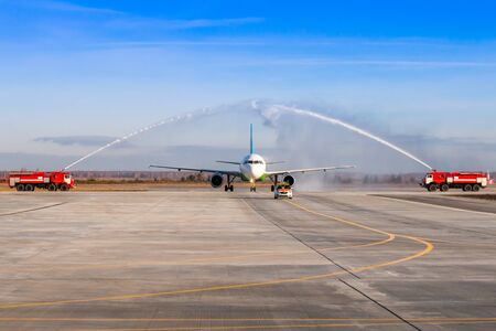 Water salute by fire truck at the airport for first visit passenger airplane. The plane moves behind the Follow-me-Car Stock Photo