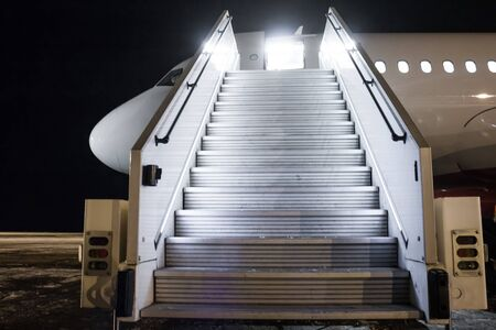 Passenger aircraft with a boarding ramp on the night airport apron