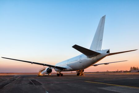 White wide body passenger aircraft at the airport apron in the evening light