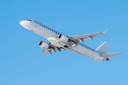 Modern white passenger airplane flies in the air on a clear sunny day against a clear blue sky