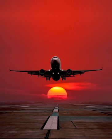 Passenger aircraft take off from airport runway against the backdrop picturesque sunrise