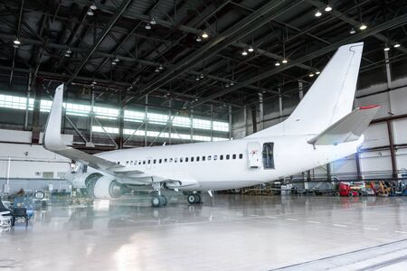 White jet plane in the hangar. Checking mechanical systems for flight operations. Passenger aircraft under maintenance