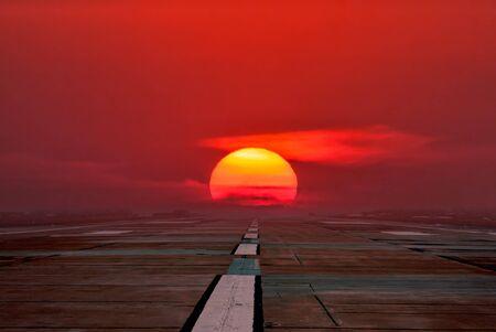 Empty airport runway in the crimson sunrise