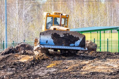 Yellow bulldozer leveling the ground at a construction site