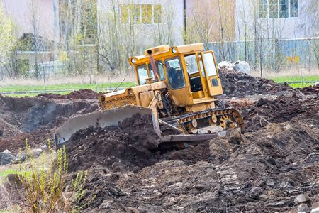 Yellow bulldozer leveling the ground at a construction site 版權商用圖片 - 146977142
