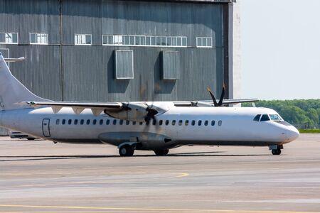 Taxiing white passenger turboprop airplane at the airport apron near hangar 版權商用圖片