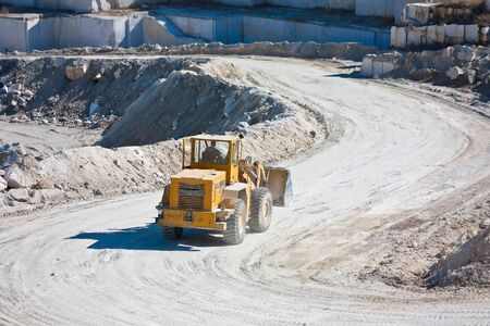 Yellow wheel tractor loader in a marble quarry