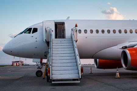 Modern passenger airplane with boarding stairs at the airport apron 版權商用圖片