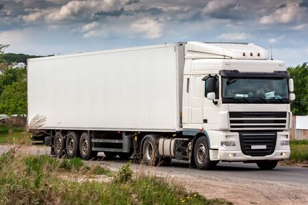 All white long-distance truck with a semitrailer moves in the countryside