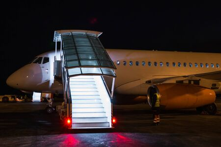 White passenger airplane with boarding steps at the night airport apron