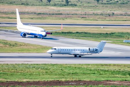 White corporate business jet moves on the airport runway. Another passenger airplane at the taxiway