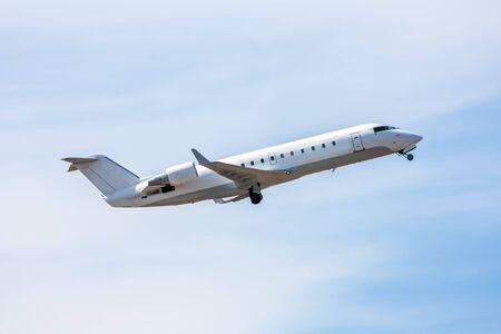 Take-off a white regional jet against a blue sky