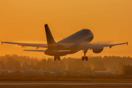 Passenger jet plane takes off in golden morning light