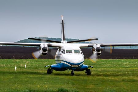 Front view of taxiing a turboprop passenger airplane at a rural airfield in cloudy summer weather