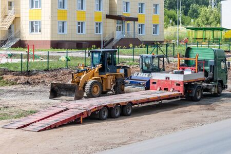 Truck with low loader, road roller and wheeled tractor on road repair