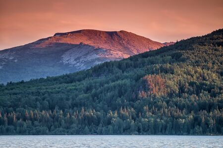 Lake, coniferous forest and mountain in the sunset light 版權商用圖片 - 149706129