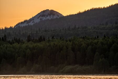 Lake, coniferous forest and mountain in the sunset light 版權商用圖片