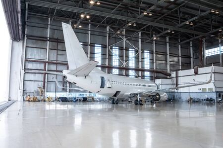 White passenger aircraft in the hangar. Airplane under maintenance. Checking mechanical systems for flight operations