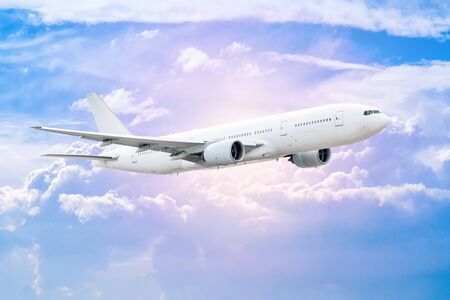 White wide-body passenger aircraft flies in the air above the clouds