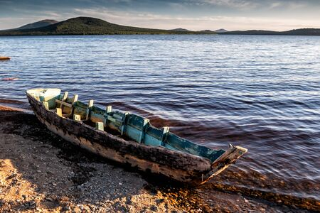 Old broken boat on the shore of a picturesque lake surrounded by low mountain ranges 版權商用圖片