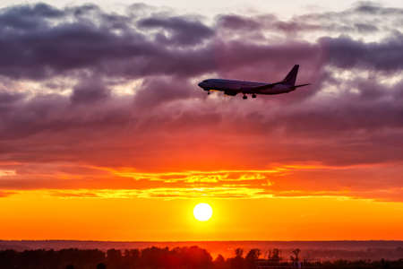 Early morning passenger airplane landing against the backdrop of a picturesque sunrise. Aircraft silhouette