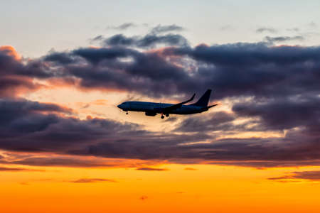 Early morning passenger aircraft flying against the backdrop of a scenic sky. Airplane silhouette
