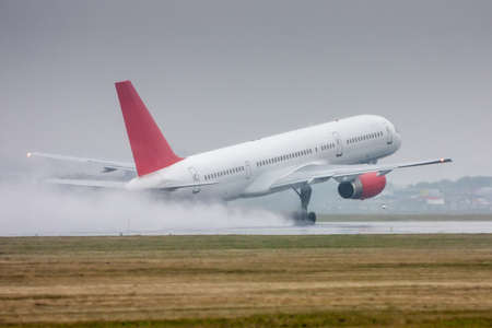 White passenger aircraft moves at the runway in heavy rain. Take-off with strong spray 版權商用圖片