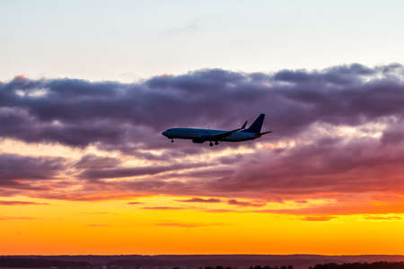 Early morning passenger airliner landing against the background of a colorful dawn sky. Jet plane silhouette