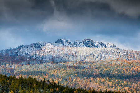 Autumn forest and rocky mountains covered with snow on a cloudy day
