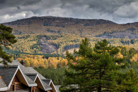 Mountains, forest and village on a cloudy autumn day
