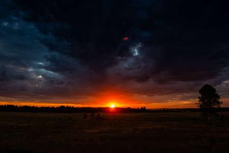 Picturesque sunset in a field after rain. Cloudy sundown sky