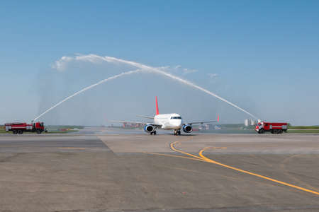 Water salute by fire truck at the airport for first visit passenger aircraft 版權商用圖片 - 154127338