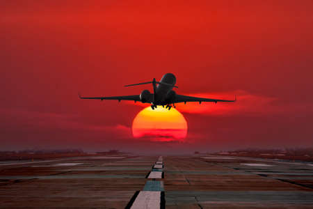 Business jet take off from airport runway against the backdrop crimson sunset 版權商用圖片 - 154865396