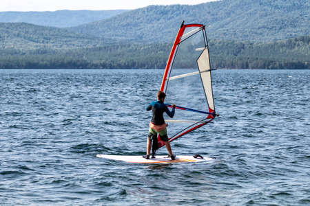 A male athlete is interested in windsurfing. He moves on a Sailboard on a large lake on a summer day 版權商用圖片