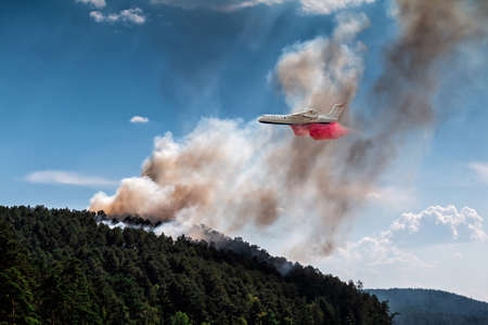 Big amphibious fire aircraft drops water on forest fire 版權商用圖片 - 156067973