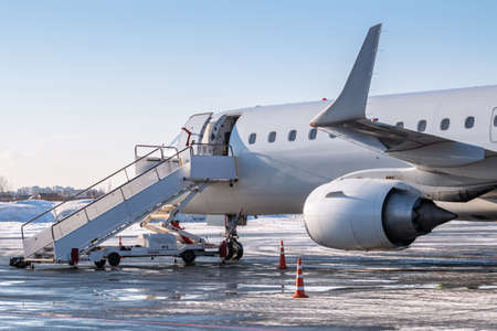 White airliner with passenger boarding stairs at the cold winter airport apron